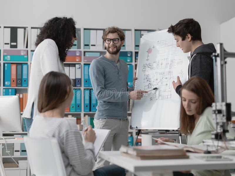 Projetando os estudantes que discutem ideias junto imagens de stock