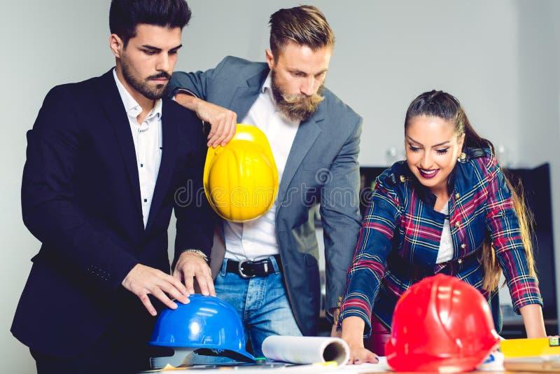 Projete a equipe do escritório de Architects que trabalha e que discute o plano da casa com os modelos e o modelo da casa fotografia de stock