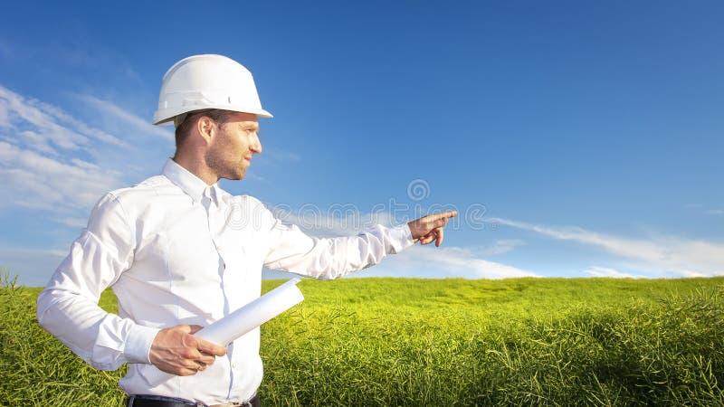Projete o arquiteto com desenhos apontam ao lugar para o canteiro de obras no dia de verão ensolarado fotos de stock royalty free