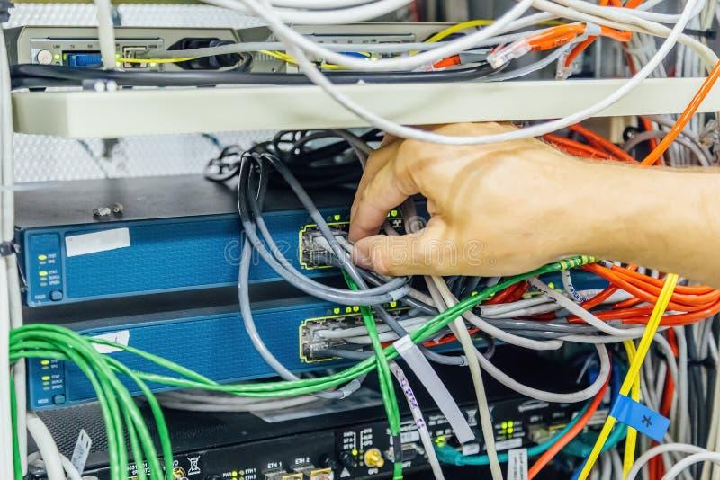 Projete o cabo de conexão da rede ao interruptor do cubo da fibra ótica para comunicações digitais na sala do servidor foto de stock