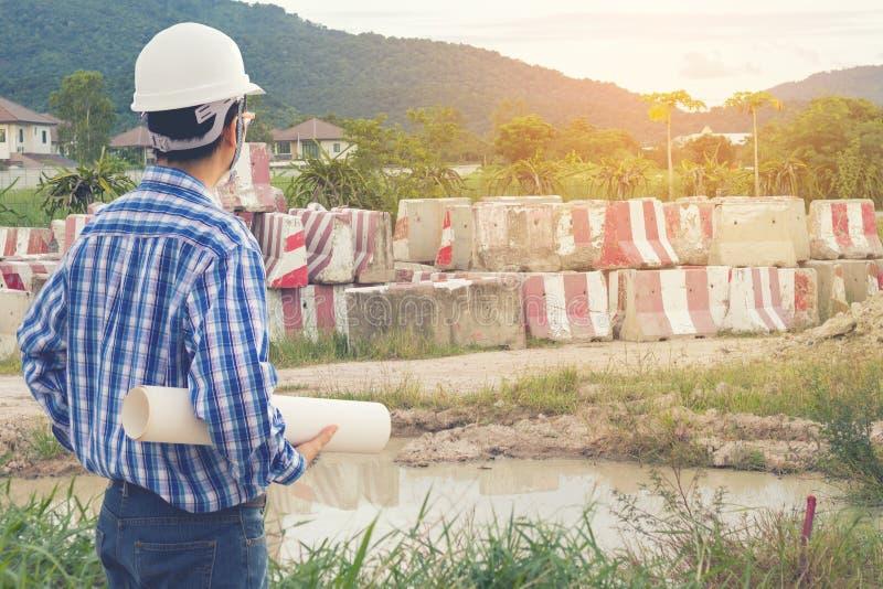 Projete o capacete branco vestindo que guarda um plano e que olha à construção foto de stock