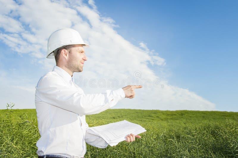 Projete o construtor com os desenhos em seus pontos das mãos ao canteiro de obras da construção geólogo em um prado verde na tard foto de stock
