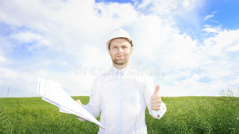 Projete o construtor com os desenhos nas mãos no prado verde pedologist no capacete branco no campo verde do verão no dia ensolar imagem de stock royalty free