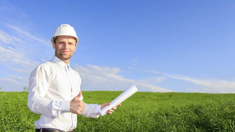 Projete o construtor no capacete branco e com os modelos no fundo verde do campo no dia ensolarado brilhante fotografia de stock royalty free