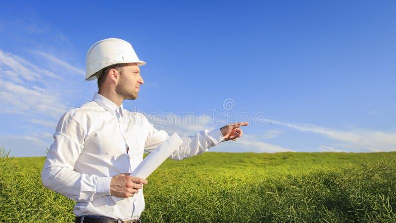Projete o construtor no capacete branco e com os modelos no fundo verde do campo no dia ensolarado brilhante que aponta sua mão à imagem de stock