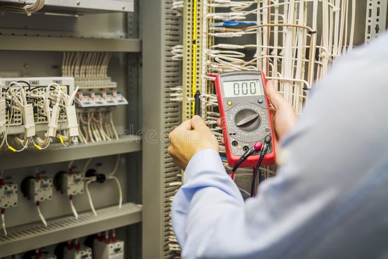 Projete o eletricista com o multímetro nas mãos no painel bonde da caixa da automatização O coordenador testa o circuito de indus foto de stock