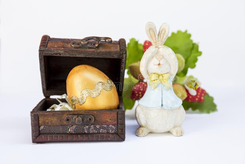 Projete o ovo dourado na caixa de madeira do tesouro com coelho de madeira engraçado imagens de stock