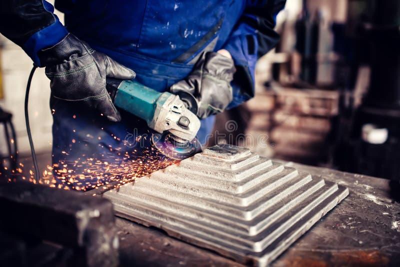 Projete o trabalho em cortar um metal e uma barra de aço com moedor de ângulo, detalhes metalúrgicos da fábrica foto de stock