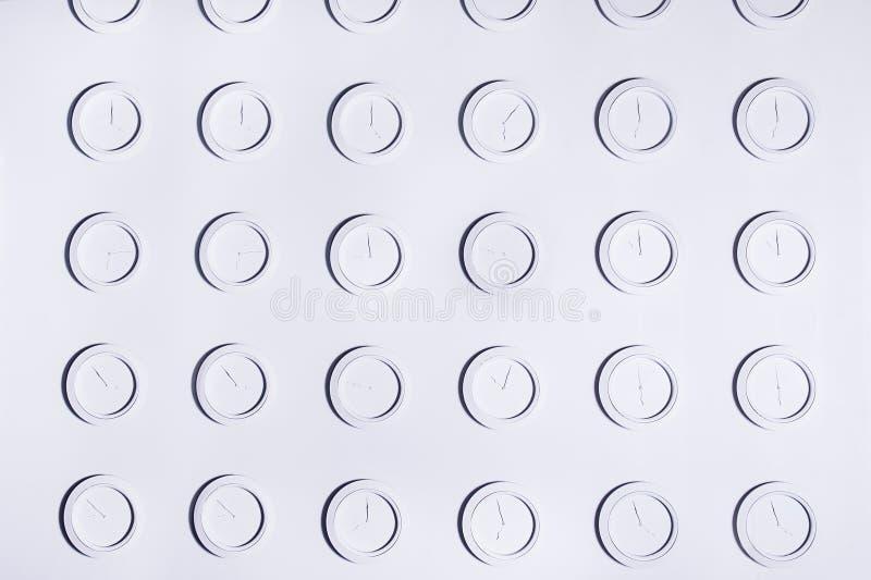 Projete a parede branca com os pulsos de disparo de parede não numerais redondos idênticos do branco Fundo do conceito do tempo imagem de stock