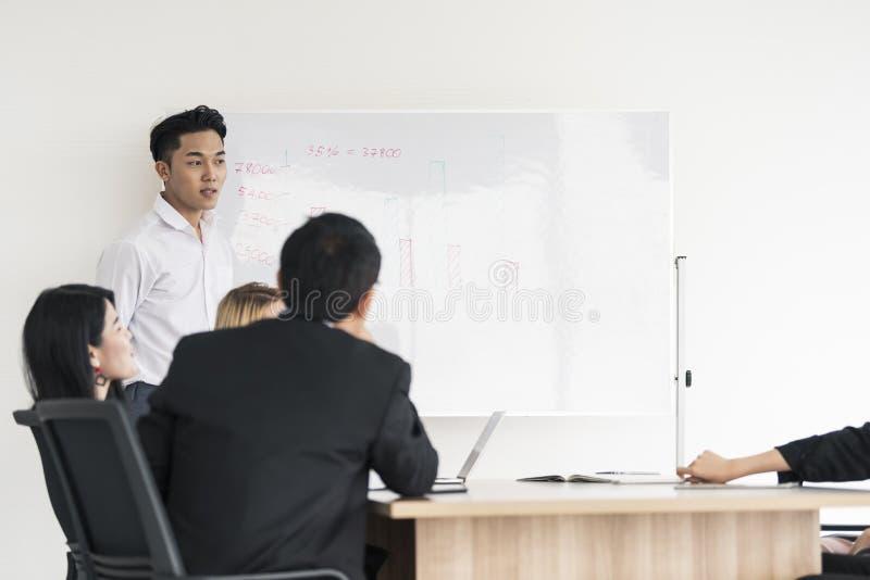 Projeto atual da placa do homem de negócios asiático novo aos colegas diversos interessados em negociações do escritório imagens de stock