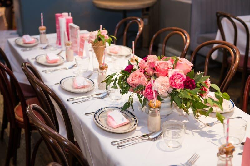 Projeto cor-de-rosa da flor na tabela servida do restaurante para o partido feminino da refeição matinal de domingo fotografia de stock
