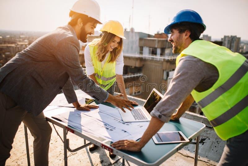 Projeto da reunião dos arquitetos, do diretor empresarial e do coordenador no terreno de construção foto de stock royalty free