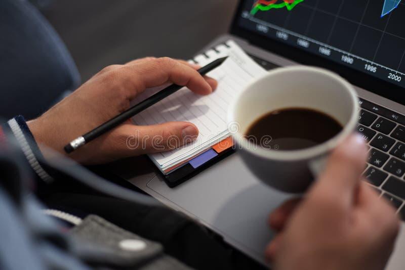 Projeto de funcionamento no portátil com café nas mãos imagem de stock royalty free