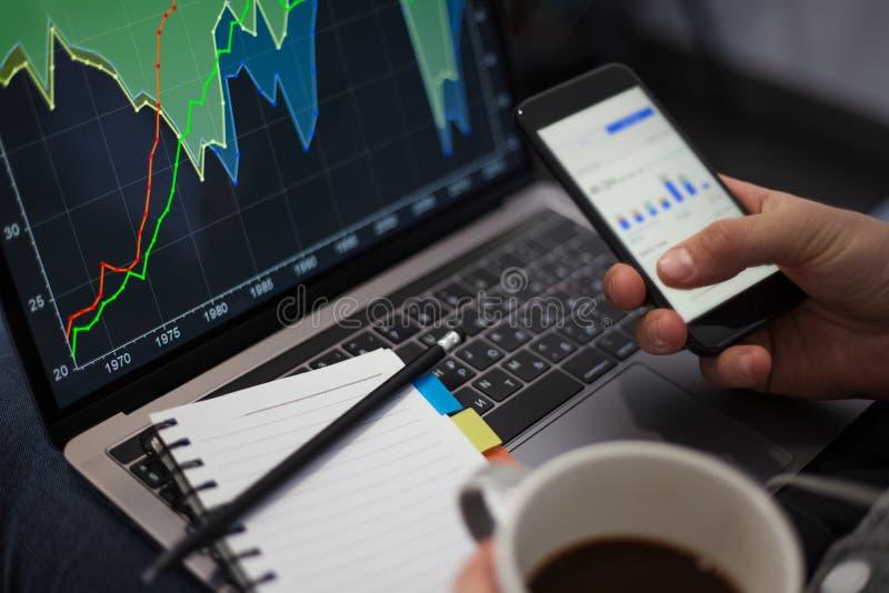 Projeto de funcionamento no portátil com smartphone e café nas mãos fotos de stock
