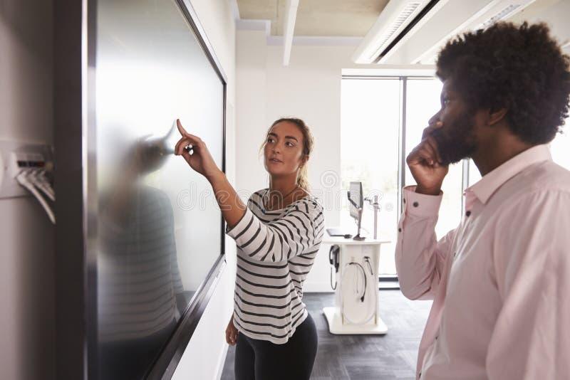 Projeto de And Tutor Discuss do estudante em Whiteboard interativo fotografia de stock royalty free