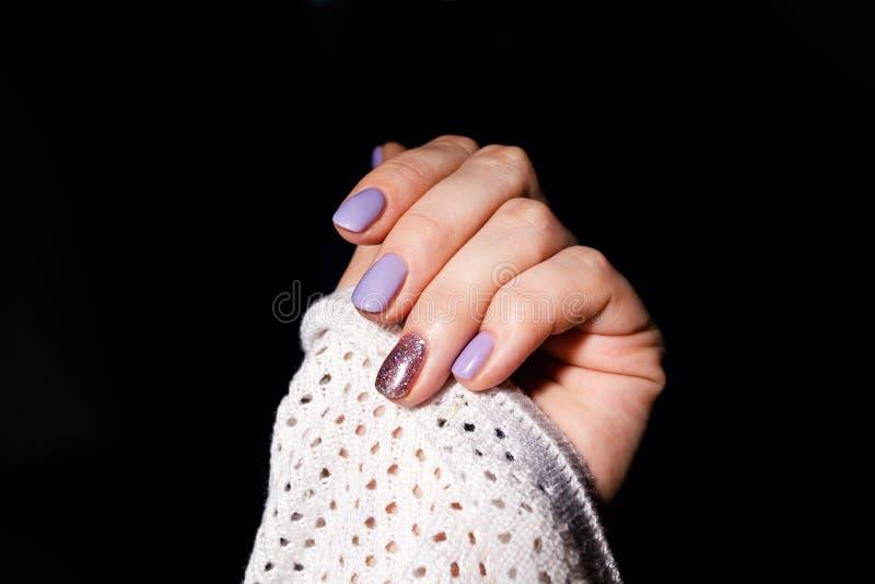 Projeto dos pregos Mãos com tratamento de mãos lilás do verão da cor em Grey Background Feche acima das m?os f?meas Prego da arte fotografia de stock