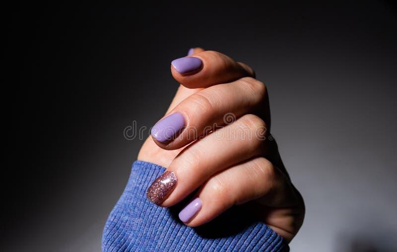 Projeto dos pregos Mãos com tratamento de mãos lilás do verão da cor em Grey Background Feche acima das m?os f?meas Prego da arte imagens de stock