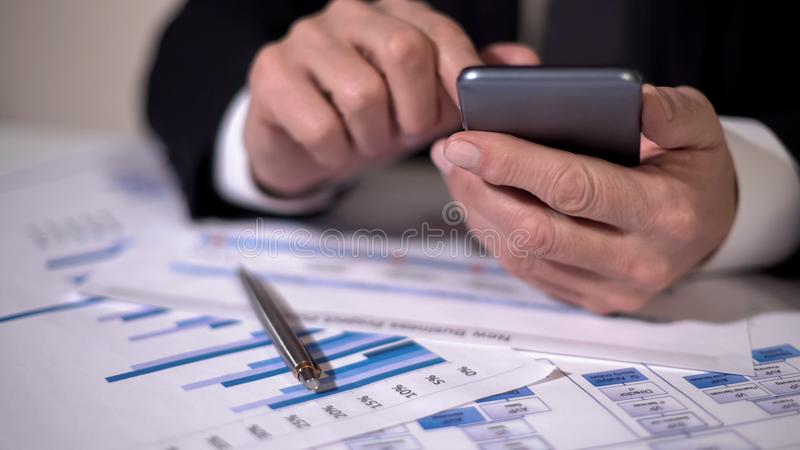 Projeto masculino do negócio do planeamento do analista em app móvel, gráficos de lucro que encontram-se ao redor imagem de stock royalty free