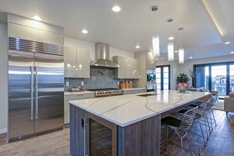 Projeto moderno lustroso da cozinha com uma ilha center cinzenta fotografia de stock