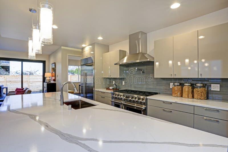 Projeto moderno lustroso da cozinha com uma ilha center longa fotografia de stock