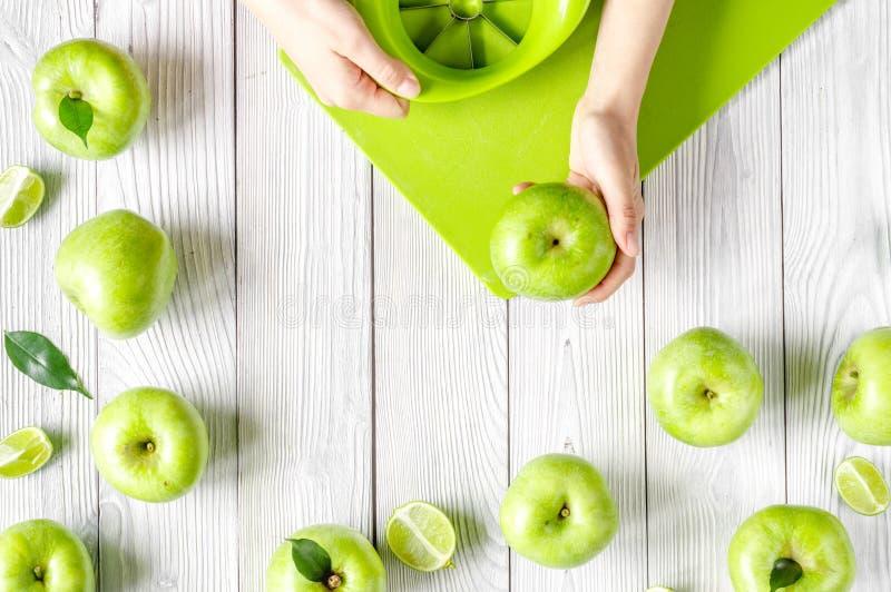 Projeto natural do alimento com as maçãs verdes do fundo branco da mesa das mãos na opinião superior fotografia de stock