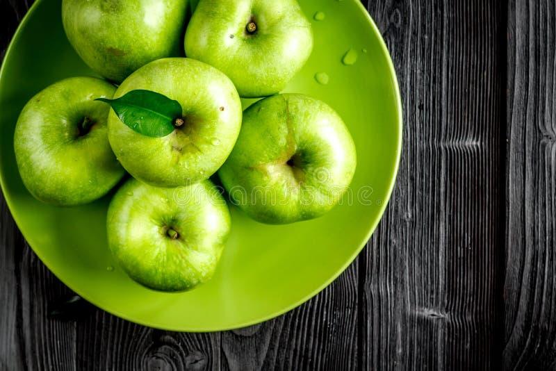 Projeto natural do alimento com as maçãs verdes do fundo escuro da mesa da placa na opinião superior imagens de stock