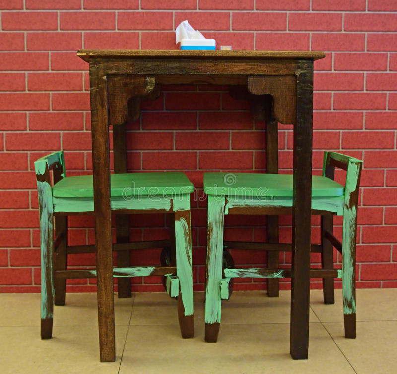 Projeto rústico da tabela e das cadeiras contra o fundo do tijolo fotos de stock
