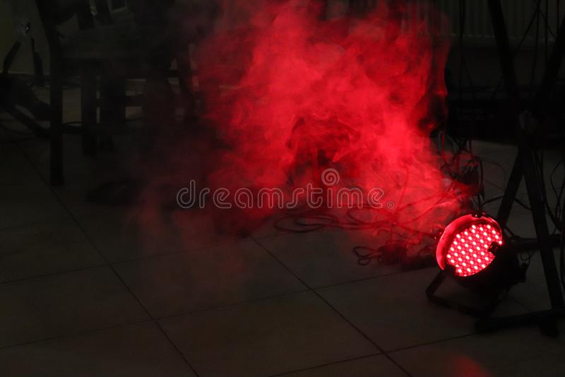 Projetor vermelho do diodo emissor de luz no assoalho com fumo na sala escura perto dos cabos e das colunas com espaço da cópia imagem de stock royalty free