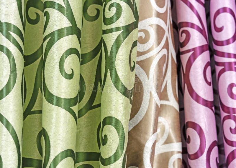 Projetos coloridos da cortina em uma janela de loja Amostras da textura de telas multi-coloridas imagens de stock