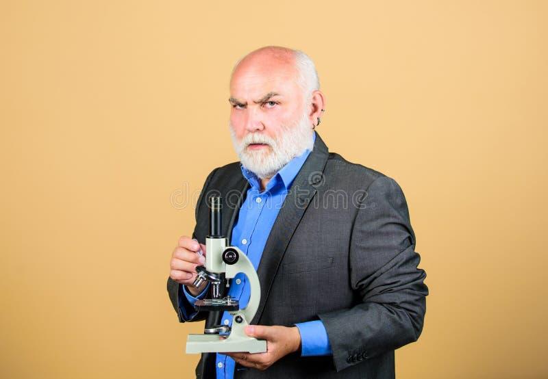 Projetos do doutorado da biologia molecular Terno formal do homem maduro com microscópio Conferente da universidade do professor  fotografia de stock royalty free