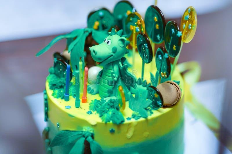Projetou sofisticada o bolo de aniversário caseiro com figura do dinossauro entre as cores dos sweeties, as verdes e as amarelas foto de stock