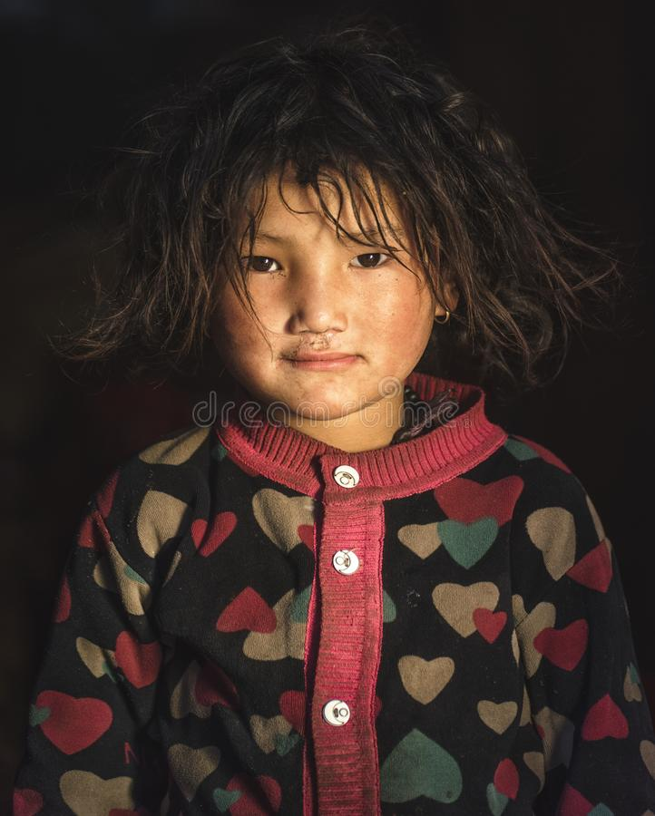 Sweet little girl indoors with curly hair. Nepalese child girl royalty free stock image