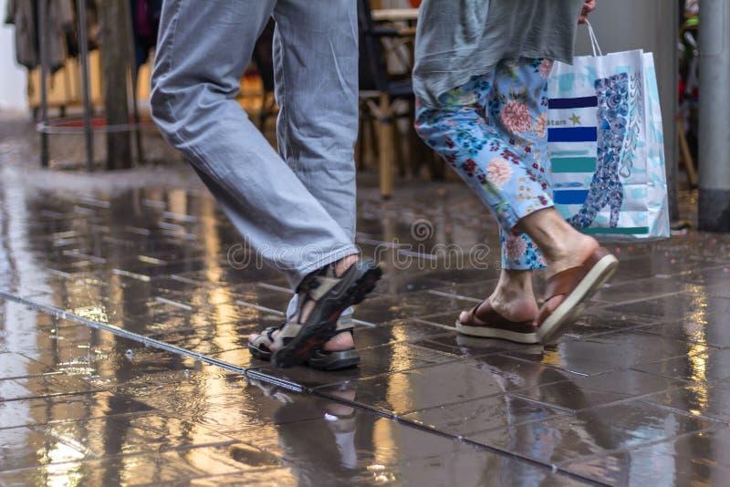 Promenad uppåt- och neråt gatan till och med regnet royaltyfri bild