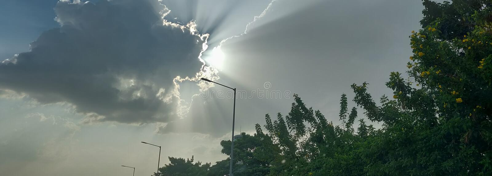 Skyscape: late afternoon view of sun rays filter through dark clouds royalty free stock photos
