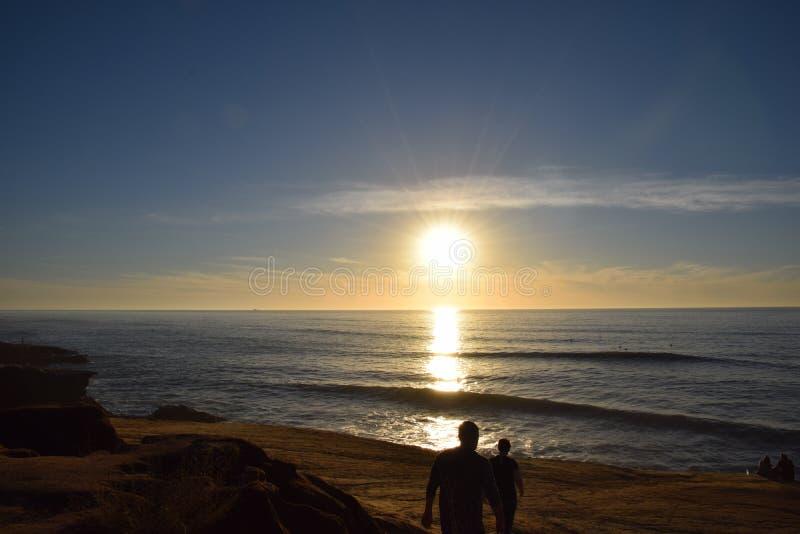 Promenade de coucher du soleil le long de plage avec des vagues photos stock