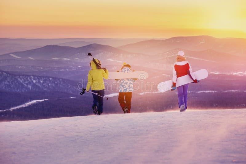Promenade de coucher du soleil de trois d'amis surfeurs de skieurs photo stock