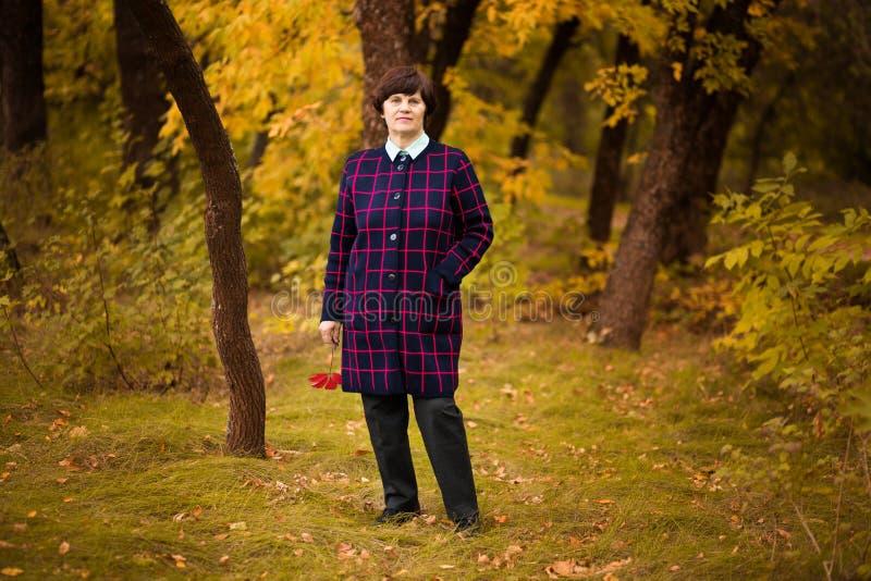 promenade de femme de 60 ans en parc d'automne d'or photo stock