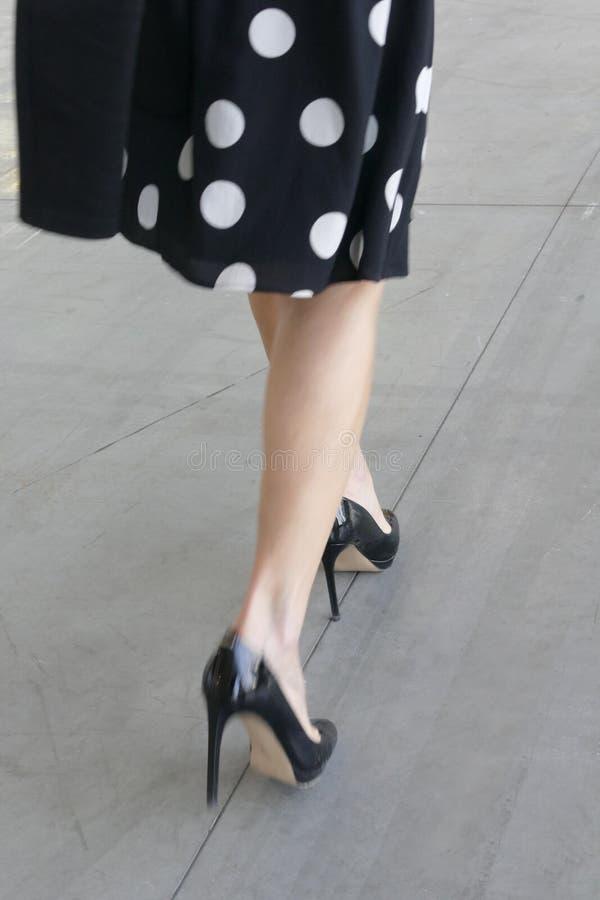 Promenade de femme habillant les chaussures noires de talons hauts image libre de droits