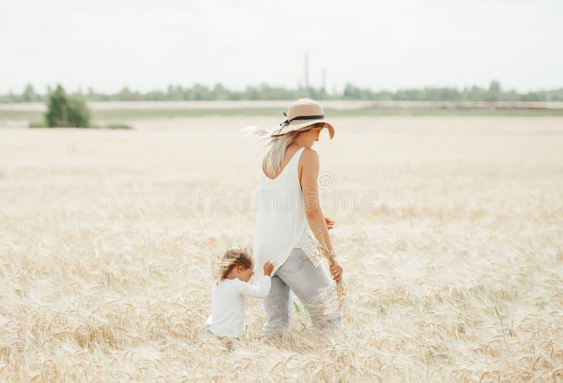 Promenade de fille de maman et de bébé dans le domaine du beau temps d'été image libre de droits