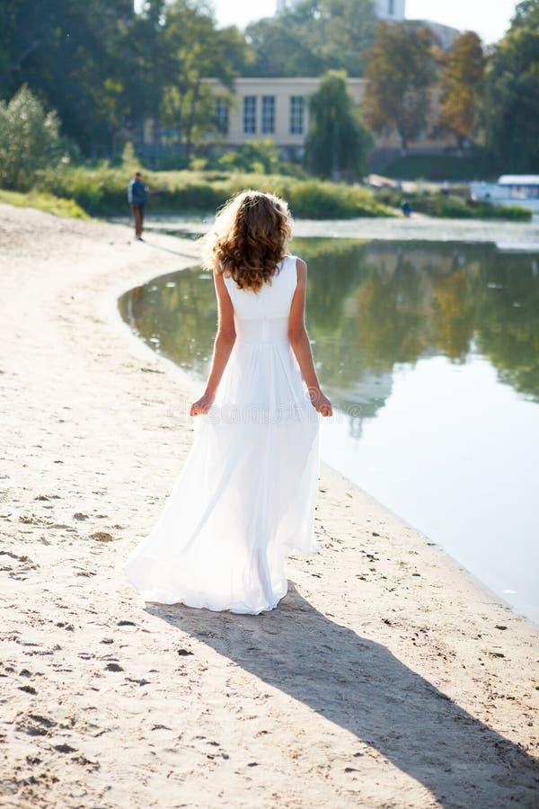 Promenade de jeune mariée de jeune fille la côte ensoleillée de la rivière images libres de droits