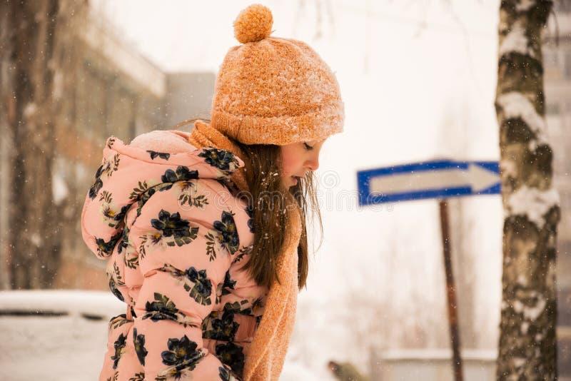 Promenade de l'hiver La fille sur la rue dans la neige photos stock