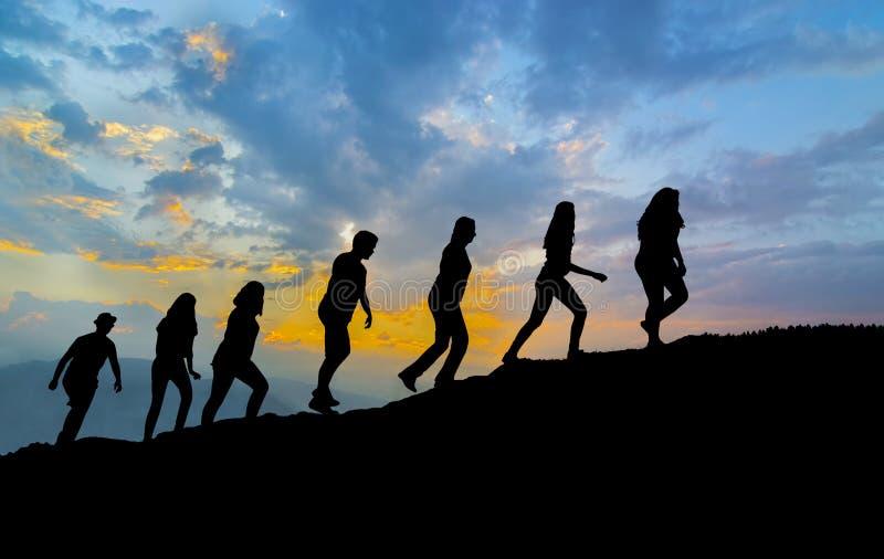Promenade de sept amis sur le chemin de montagne dans le coucher du soleil photos libres de droits