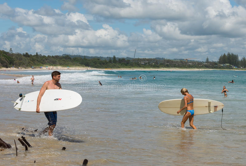 Promenade de surfers dans la plage de Byron Bay photos stock