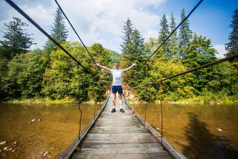 Promenade de touristes d'homme par le long pont suspendu en bois au-dessus du riv photo libre de droits