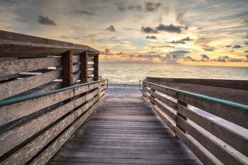 Promenade, die zu den Ozean an Vanderbilt-Strand bei Sonnenuntergang führt stockfoto