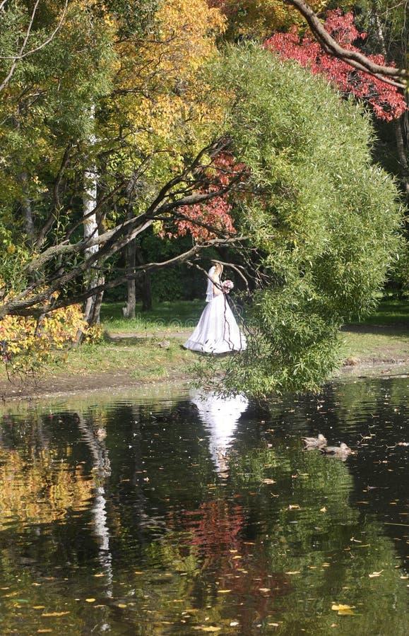 Promenade en parc en automne R?flexion dans l'eau Jeune mari?e photographie stock libre de droits