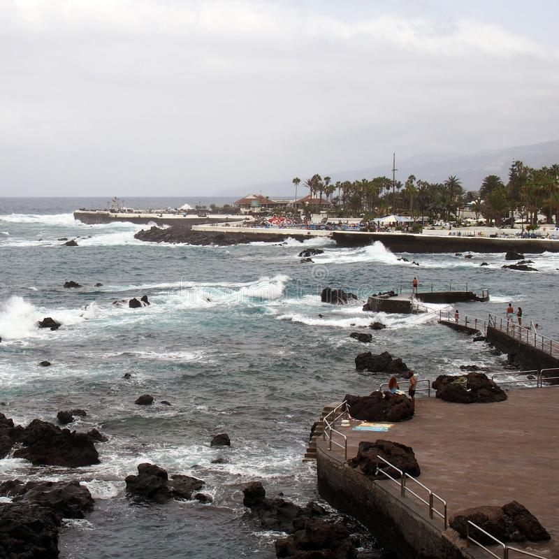 the promenade and lido at puerto de la cruz in tenerife with people on the seafront and dramatic waves breaking over the coastal stock photography