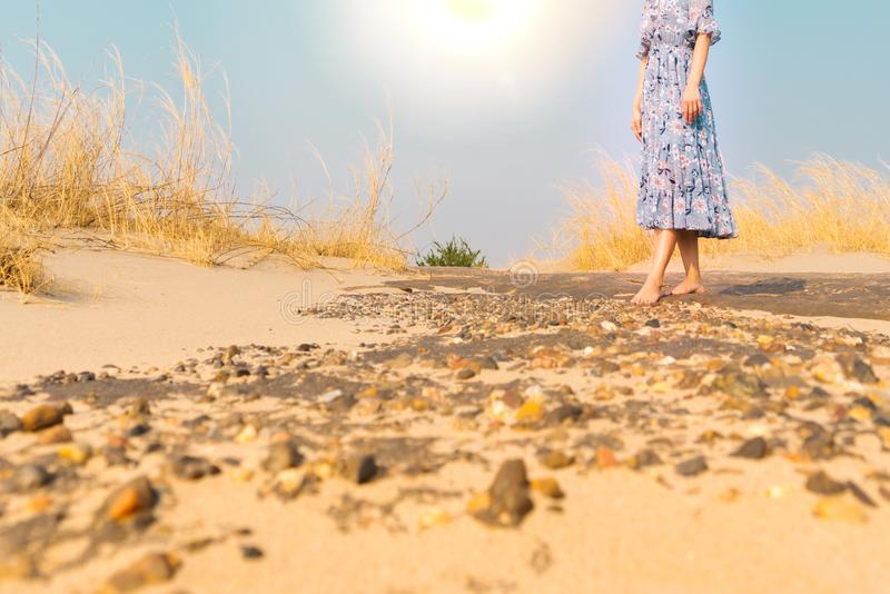 Promenade malheureuse de femme de pied nu sur seule la route de sable de roche photo libre de droits