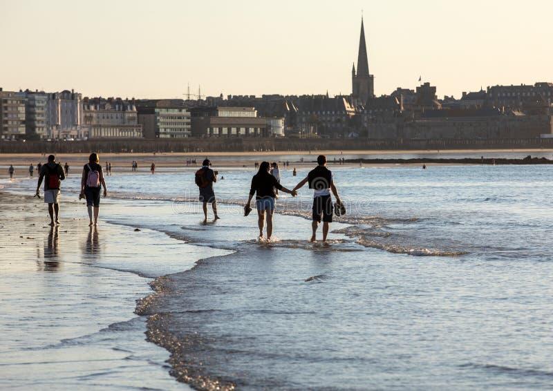 Promenade romantique des personnes avant coucher du soleil sur la plage pittoresque de Saint Malo Brittany, France image stock