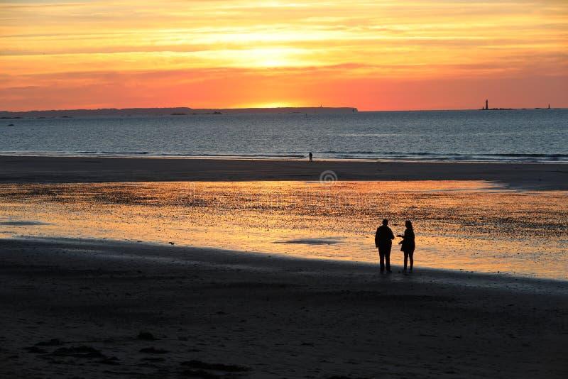 Promenade romantique des personnes avant coucher du soleil sur la plage pittoresque de Saint Malo Brittany, France photographie stock